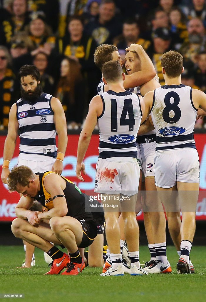 200 gamer Jack Riewoldt of the Tigers looks dejected after defeat as fellow 200 gamer Harry Taylor of the Cats is hugged by teammates during the...