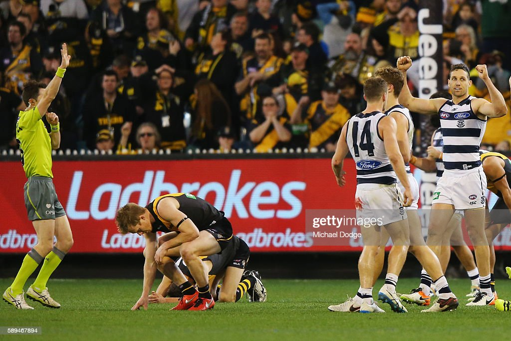 200 gamer Jack Riewoldt of the Tigers looks dejected after defeat as fellow 200 gamer Harry Taylor of the Cats celebrates the win with arms up during...