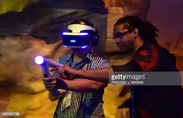 A gamer receives assistance playing 'Farpoint' while wearing Playstation VR Morpheus at the Los Angeles Convention Center during the 2016 Electronic...