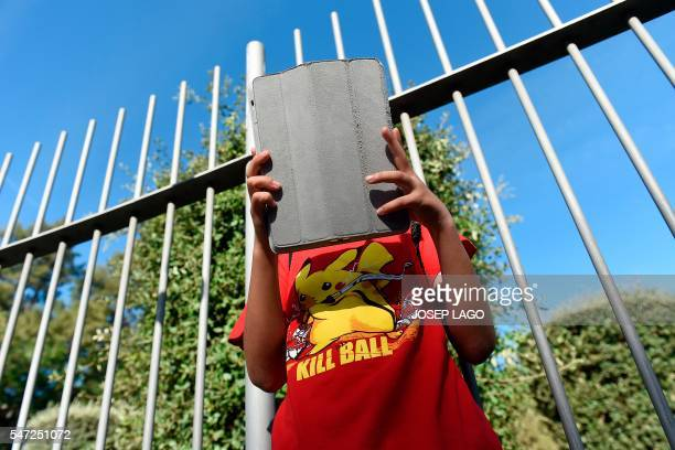 TOPSHOT A gamer uses the Pokemon Go application on his tablet in a Barcelona park on July 14 2016 / AFP / JOSEP LAGO