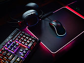gamer workspace concept, top view a gaming gear, mouse, keyboard with RGB Color, joystick, headset, webcam, VR Headset on black table background.
