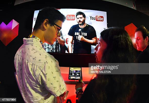 Gamers discuss a tablet computer demonstrating YouTube's venture into game streaming called 'YouTube Gaming' on the second day of the Electronic...