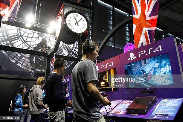Gamers play the video game 'Assassin's Creed Syndicate' developed by Ubisoft on PlayStation games consoles PS4 at Paris Games Week a trade fair for...