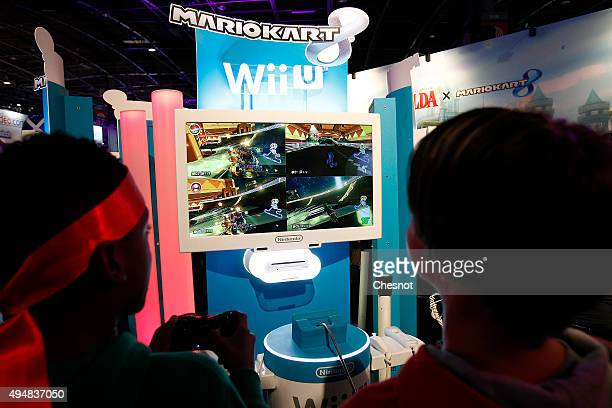 Gamers play the video game 'Mario Kart 8' developed by Nintendo EAD on a games console Nintendo Wii U at Paris Games Week a trade fair for video...