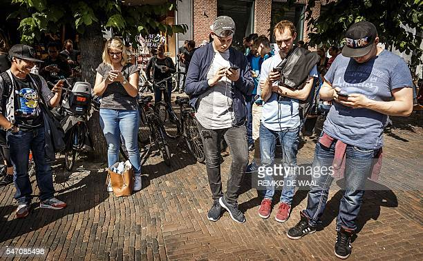 Gamers play with the Pokemon Go application on their mobile phone at the Grote Markt in Haarlem on July 13 2016 / AFP / ANP / Remko de Waal /...