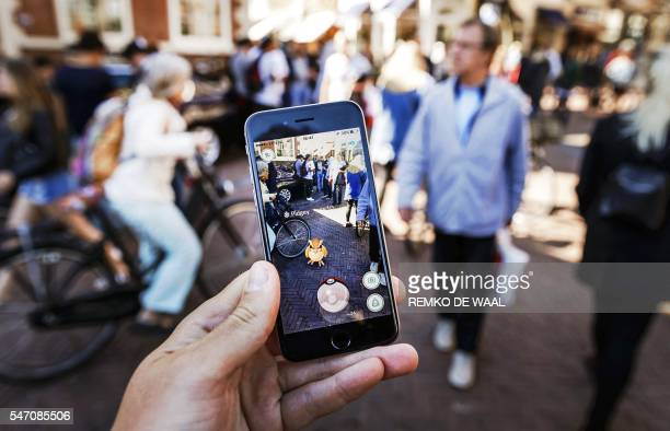 TOPSHOT Gamers play with the Pokemon Go application on their mobile phone at the Grote Markt in Haarlem on July 13 2016 / AFP PHOTO / ANP / Remko de...
