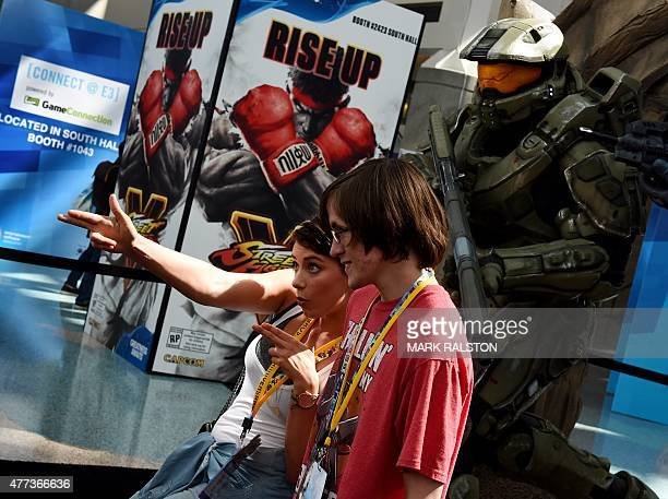 Gamers pose for photos in front of action figures from the 'Halo' game on the opening day of the Electronic Entertainment Expo known as E3 in Los...