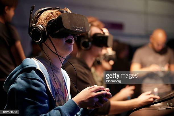 Gamers wear highdefinition virtual reality headsets manufactured by Oculus VR Inc as they play Gaijin Entertainment's 'War Thunder' video game on...