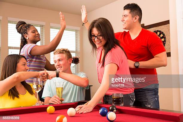 Games: Multi-ethnic group friends play pool, enjoy round of drinks.