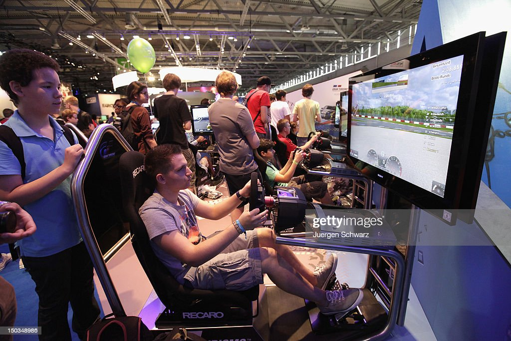 Gaming enthusiasts play Grand Turismo at the Gamescom 2012 gaming trade fair on August 16, 2012 in Cologne, Germany. Gamescom is Europe's largest gaming expo with 600 international developers exhibiting their latest products. Around 250,000 visitors are expected to attend the four-day event being held between August 15-19.