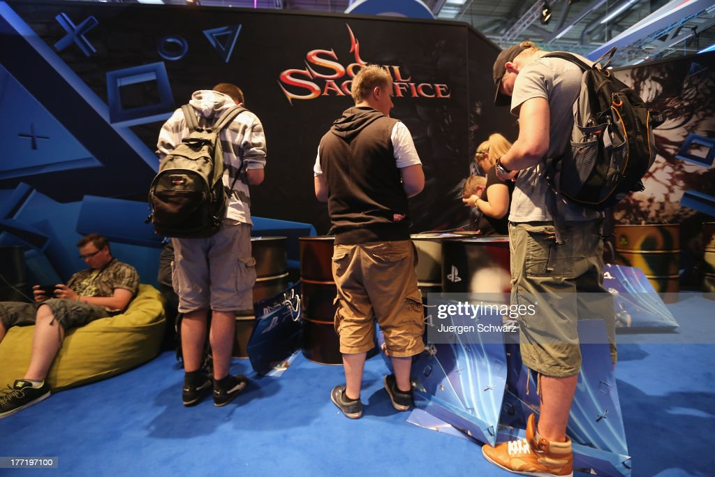 Gaming enthusiasts try out games on Sony Playstation at the Gamescom 2013 gaming trade air on August 22, 2013 in Cologne, Germany. Gamescom is the world's largest trade fair for digital gaming and will be open to the public from August 22-25.