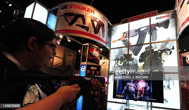 A gaming fan samples the AK Striker a realistic AK47 replica on the second day of the E3 videogame extravaganza in Los Angeles on June 6 2012 in...