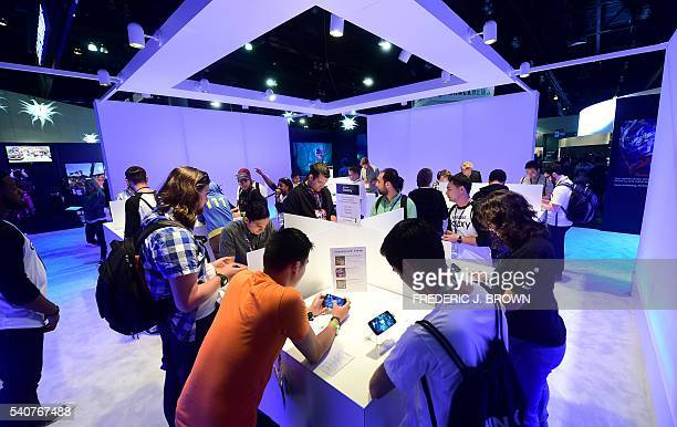 Gaming fans play 'Need for Speed' on Samsung Galaxy S7 mobile phones at the Los Angeles Convention Center on June 16 2016 in Los Angeles California...