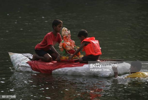 Ganeshotsav Ganesh idols Ganpati Immersion Visarjan Devotion to the Elephant God a devotee pays a fare well to Lord Ganesh by immersing the idol at...