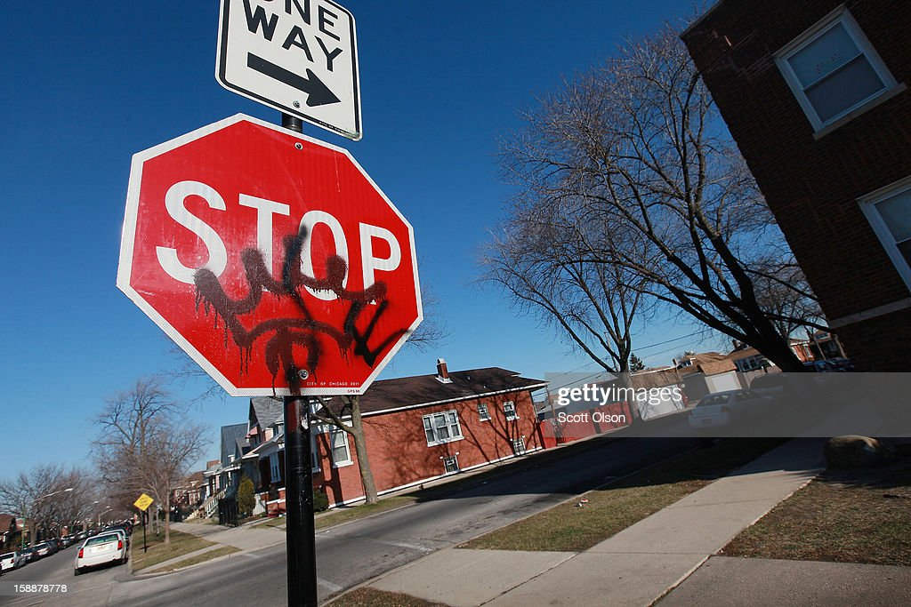 Gang graffiti is painted on a stop sign on the 5800 block of South Sacramento Avenue near the spot where 19-year-old Devonta Grisson was killed in a drive-by shooting on New Year's Day, on January 2, 2013 in Chicago, Illinois. Grisson was one of fifteen people shot in Chicago on the first day of the year, three fatally. While Chicago saw more than 500 murders last year, Aurora, Illinois' second largest city, had no murders in 2012.