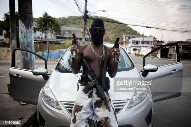 A gang member also known as Trafficante poses with his weapons in Villa Allianca one of the many non pacified favelas of Rio de Janeiro February 8...