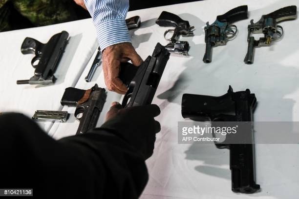 A gang member hands over his gun to Cali's Mayor Maurice Armitage during a ceremony in the framework of the 'Arms for opportunities' disarmement...