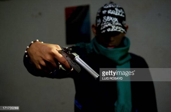 A gang member poses with a homemade gun at the Siloe neighborhood in Cali Colombia on June 27 2013 Siloe is one of the most dangerous neighborhoods...