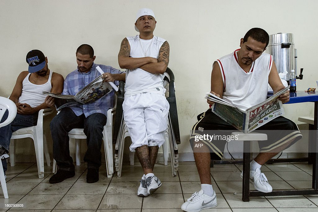 Gang members read the newspaper after a press conference where leaders of the five gangs --Mara Salvatrucha (MS-13), Barrio 18, MAO-MAO, Máquina and Mirada Locos-- demand the US to support the truce they started on 2012 --which had already lowered the daily murder rate from 14 to 5-- on January 28, 2013 at La Esperanza prison in San Salvador. The US State Department recently issued a travel warning to US citizens about the security situation in El Salvador. The leaders have assured tourists their safety and well-being while visiting the country and have given instructions to their members to respect them. AFP PHOTO/ Juan CARLOS