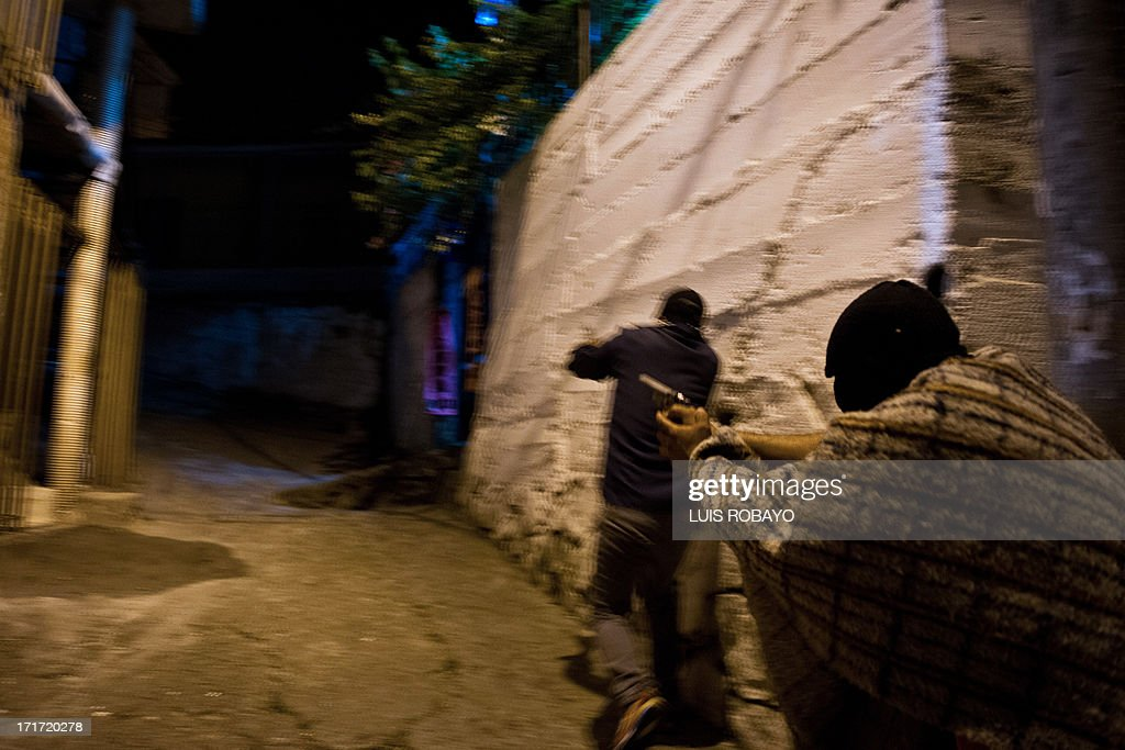 Gang members run in a hurry after listening gunshots at the Siloe neighborhood in Cali, Colombia on June 27, 2013. Siloe is one of the most dangerous neighborhoods of the city, where more than 20 gangs battle for territories. AFP PHOTO/LUIS ROBAYO