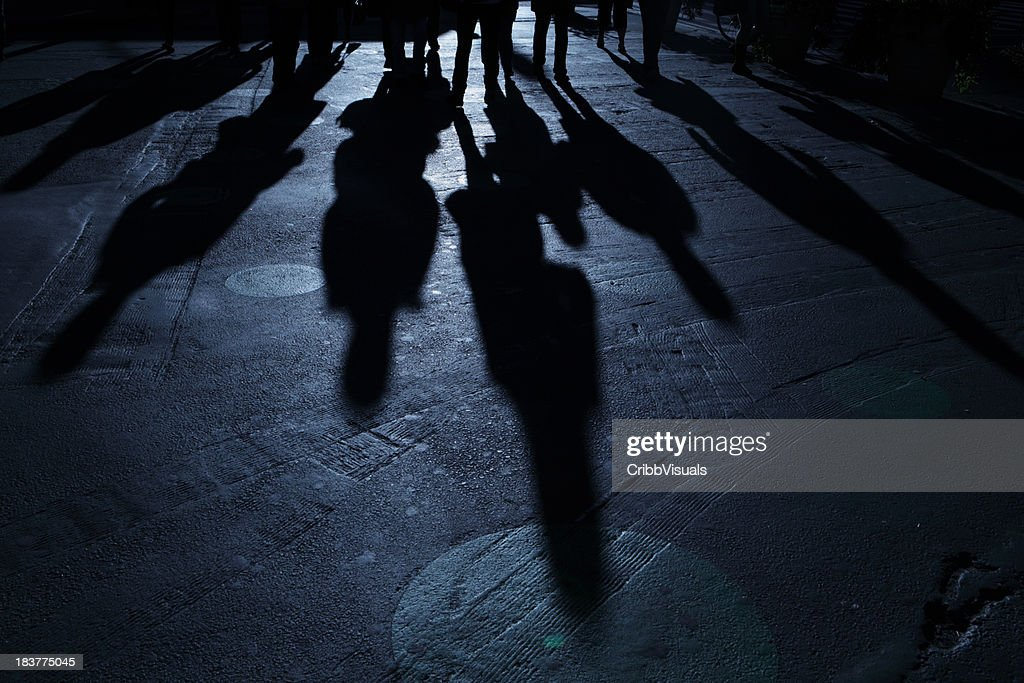Gang of people advancing on viewer blue night shadows