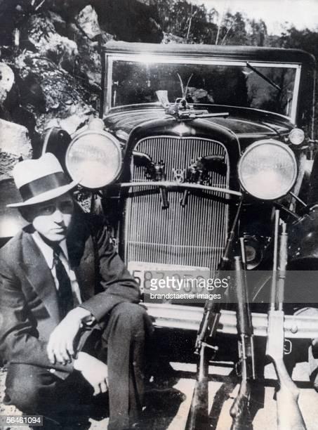 Gangster Clyde Barrow kneeing besides his automobile Photography [Der Verbrecher Clyde Barrow bewaffnet vor seinem Auto Photographie]