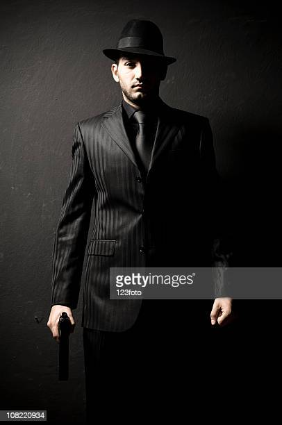 Gangster Man In Black Suit and Hat Holding Gun