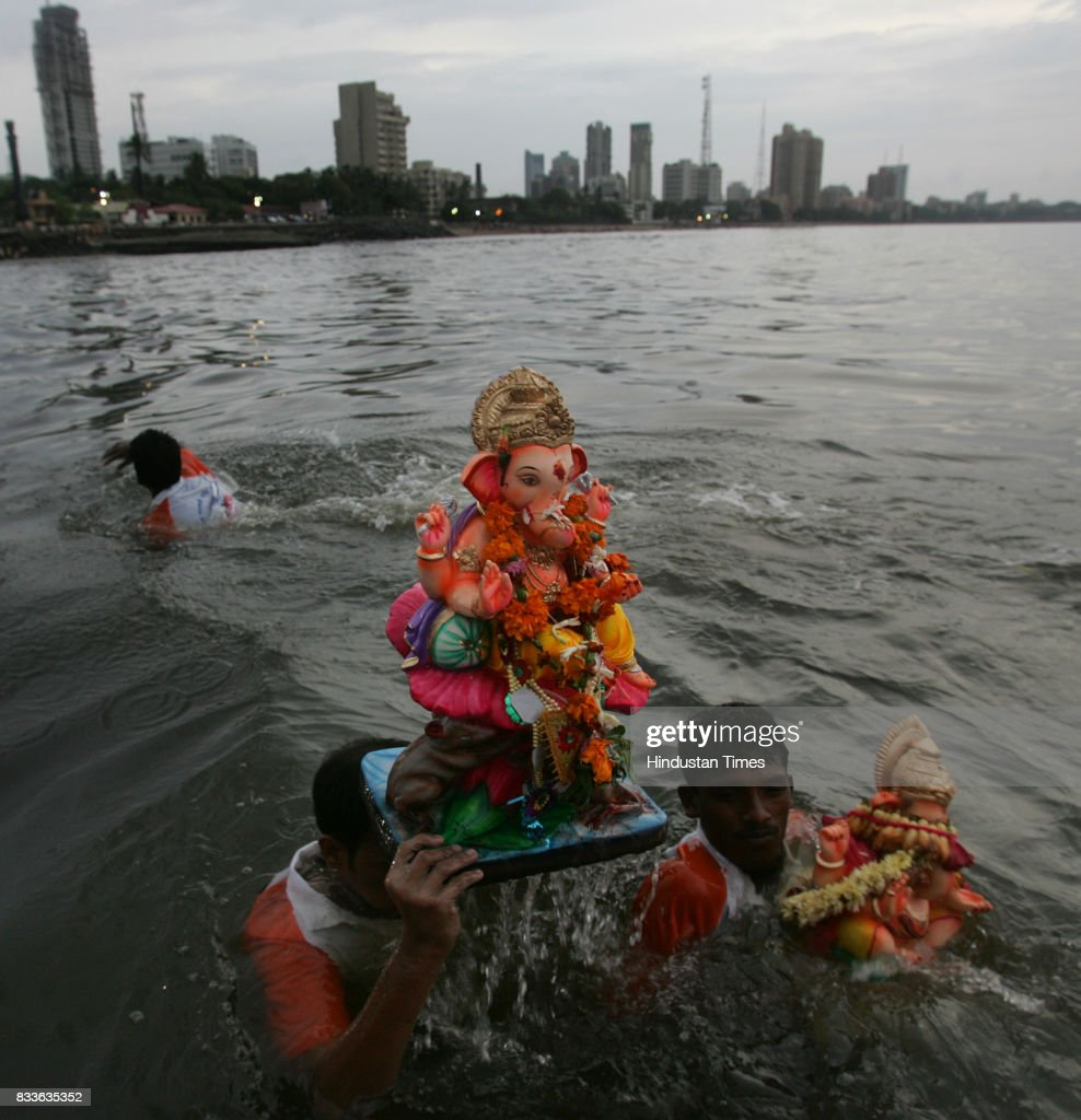 Volunteers escorts the city's favorite God into the sea at Dadar Chowpatty on Monday.