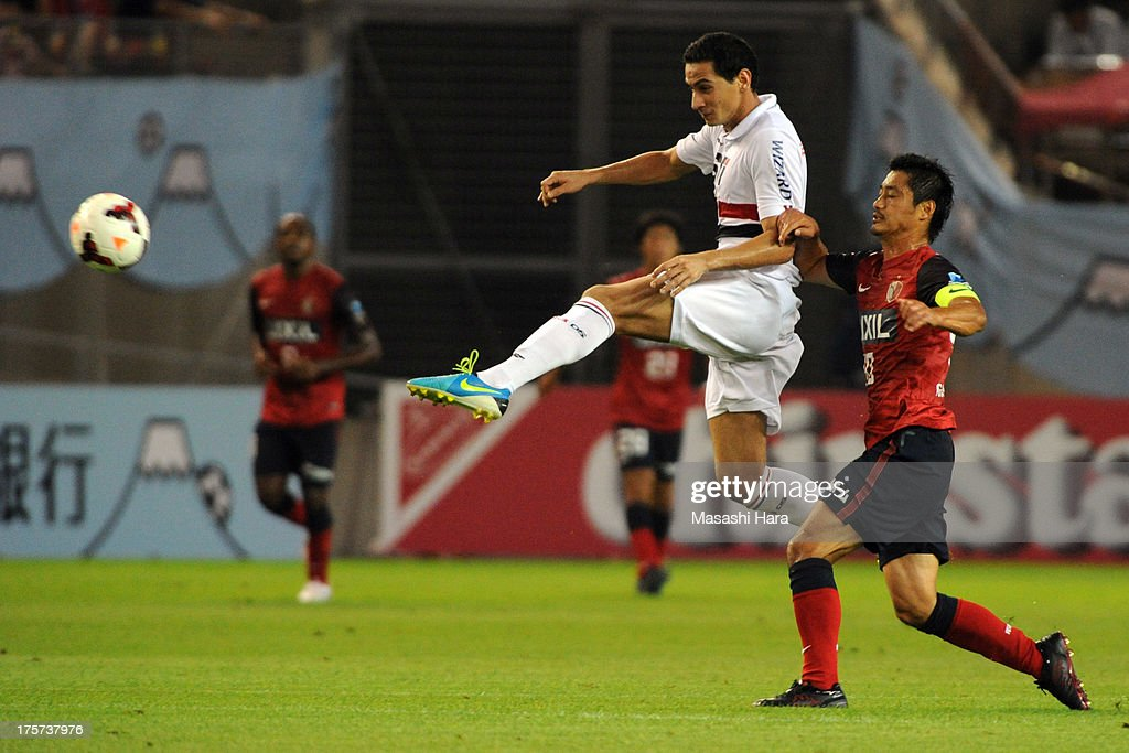 Ganso #8 of Sao Paulo FC and <a gi-track='captionPersonalityLinkClicked' href=/galleries/search?phrase=Mitsuo+Ogasawara&family=editorial&specificpeople=546862 ng-click='$event.stopPropagation()'>Mitsuo Ogasawara</a> #40 of Kashima Antlers compete for the ball during the Suruga Bank Championship match between Kashima Antlers and Sao Paulo FC at Kashima Soccer Stadium Stadium on August 7, 2013 in Kashima, Ibaraki, Japan.
