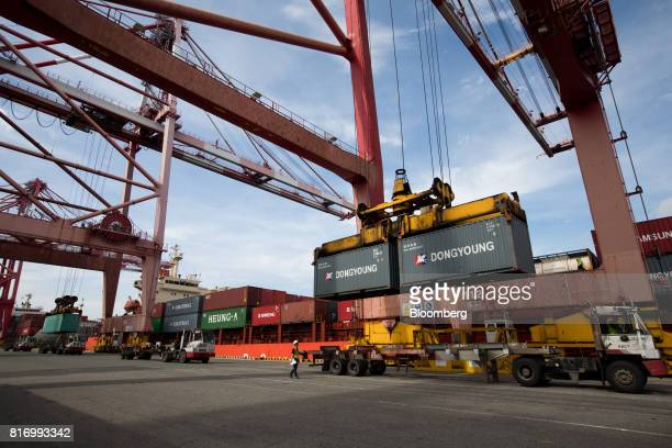 A gantry crane loads Dong Young Shipping Co shipping containers onto a truck at the Busan Port Terminal in Busan South Korea on Monday July 17 2017...