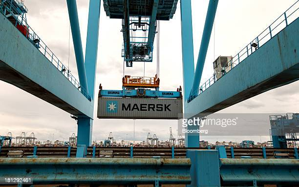 A gantry crane transports a shipping container from the vessel Maersk Seoul operated by AP MoellerMaersk A/S at the APM Terminal in the Port of...