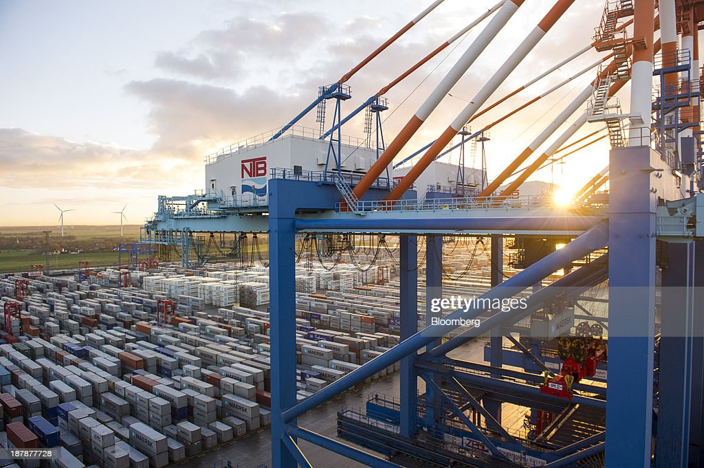 Gantry cranes and shipping containers stand on the dockside beside the Maersk Mc-Kinney Moeller Triple-E Class container ship, operated by A.P. Moeller-Maersk A/S, in the Port of Bremerhaven in Bremerhaven, Germany, on Monday, Nov. 11, 2013. A.P. Moeller-Maersk A/S's container-shipping line, the world's largest, reported an 11 percent increase in third-quarter profit after cost cuts countered a decline in freight rates. Photographer: Kristian Helgesen/Bloomberg via Getty Images
