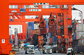 Gantry cranes transport shipping containers at a shipping terminal in Tokyo Japan on Tuesday April 21 2015 US and Japanese officials failed to reach...
