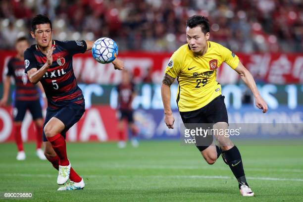 Gao Lin of Guangzhou Evergrande and Naomichi Ueda of Kashima Antlers vie for the ball during the AFC Champions League Round of 16 match between...