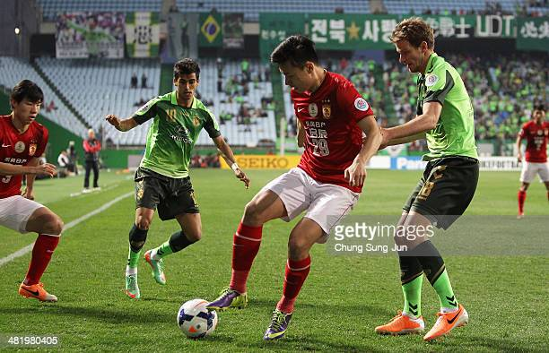Gao Lin of Guangzhou Evergrande compete for the ball with Leonardo and Alex Wilkinson of Jeonbuk Hyundai Motors during the AFC Champions League Group...