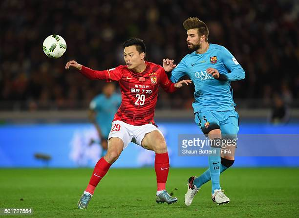 Gao Lin of Guangzhou Evergrande FC shields the ball from Gerard Pique of Barcelona during the FIFA Club World Cup Semi Final match between Barcelona...