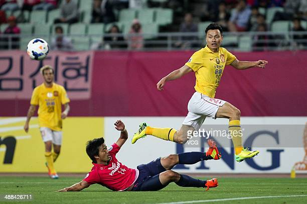 Gao Lin of Guangzhou Evergrande passes the ball in front of Yusuke Maruhashi of Cerezo Osaka during the AFC Asian Champions League 2014 Round of 16...