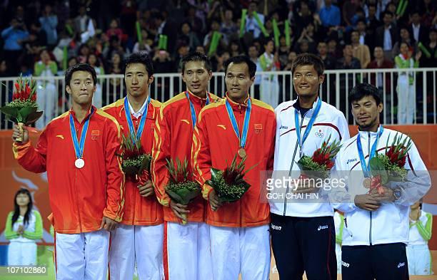 Gao Peng Li Jian Xu Linyin and Wu Penggen of China Kentaro Asahi and Katsuhiro Shiratori of Japan pose with their medals during the award ceremony in...