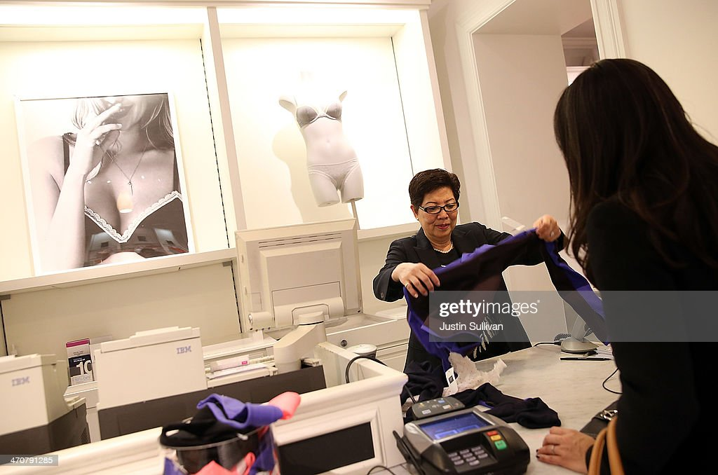 Gap employee Kim Nguyen helps a customer at a Gap store on February 20 2014 in San Francisco California Gap Inc announced that they will raise their...
