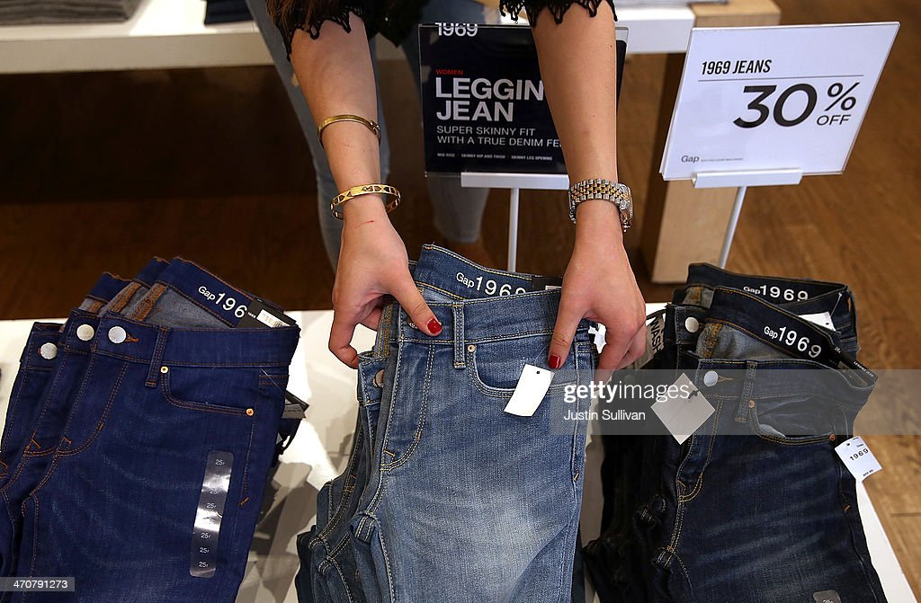 Gap employee Shinju NozawaAuclair fixes a display of jeans at a Gap store on February 20 2014 in San Francisco California Gap Inc announced that they...