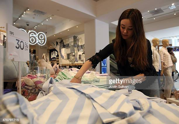 Gap employee Shinju NozawaAuclair folds clothes at a Gap store on February 20 2014 in San Francisco California Gap Inc announced that they will raise...
