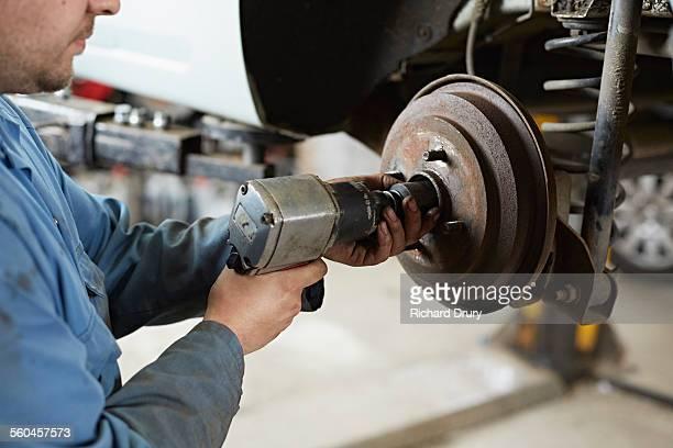 Garage mechanic removing hub nut