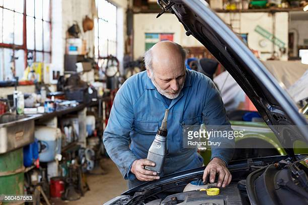 Garage mechanic topping up engine oil