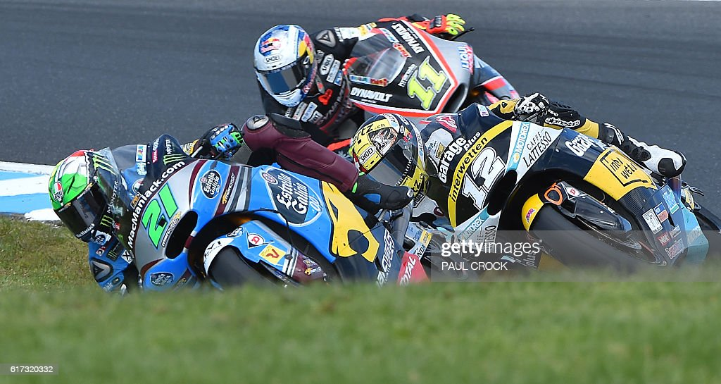 Garage Plus Interwetten Kalex rider Thomas Luthi of Switerland (C) races against Marc VDS rider Franco Morbidelli of Italy (L) and Dynavolt Intact GP rider Sandro Cortese of Germany (R) for the lead on the last lap of the Australian Moto2 race at Phillip Island on October 23, 2016. / AFP / PAUL