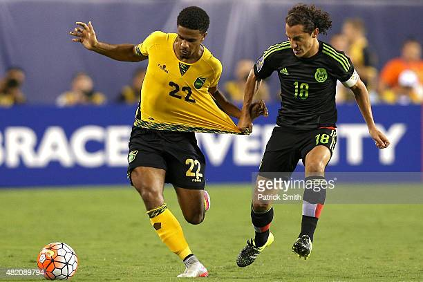 Garath McClearly of Jamaica battles for the ball with Andres Guardado of Mexico in the in the first half during the CONCACAF Gold Cup Final at...