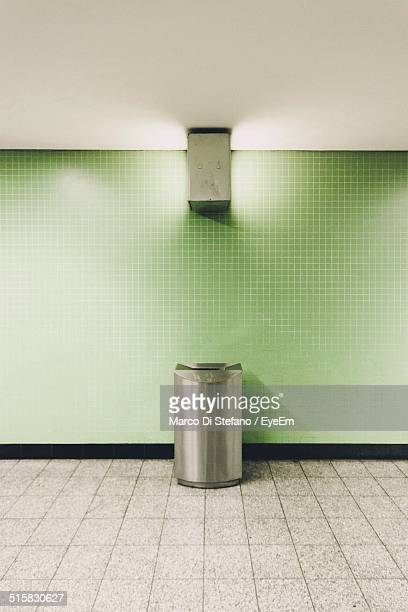 Garbage Bin Against Green Wall