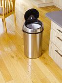 Garbage bin in kitchen setting.