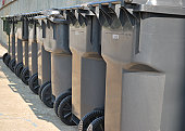 9 garbage cans neatly lined up, waiting for pickup.
