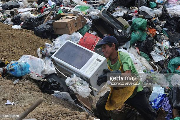 A garbage classifier retrieves a microwave on June 1 2012 in the garbage dump in Garabito 120 km south of San Jose AFP PHOTO/ Rodrigo ARANGUA