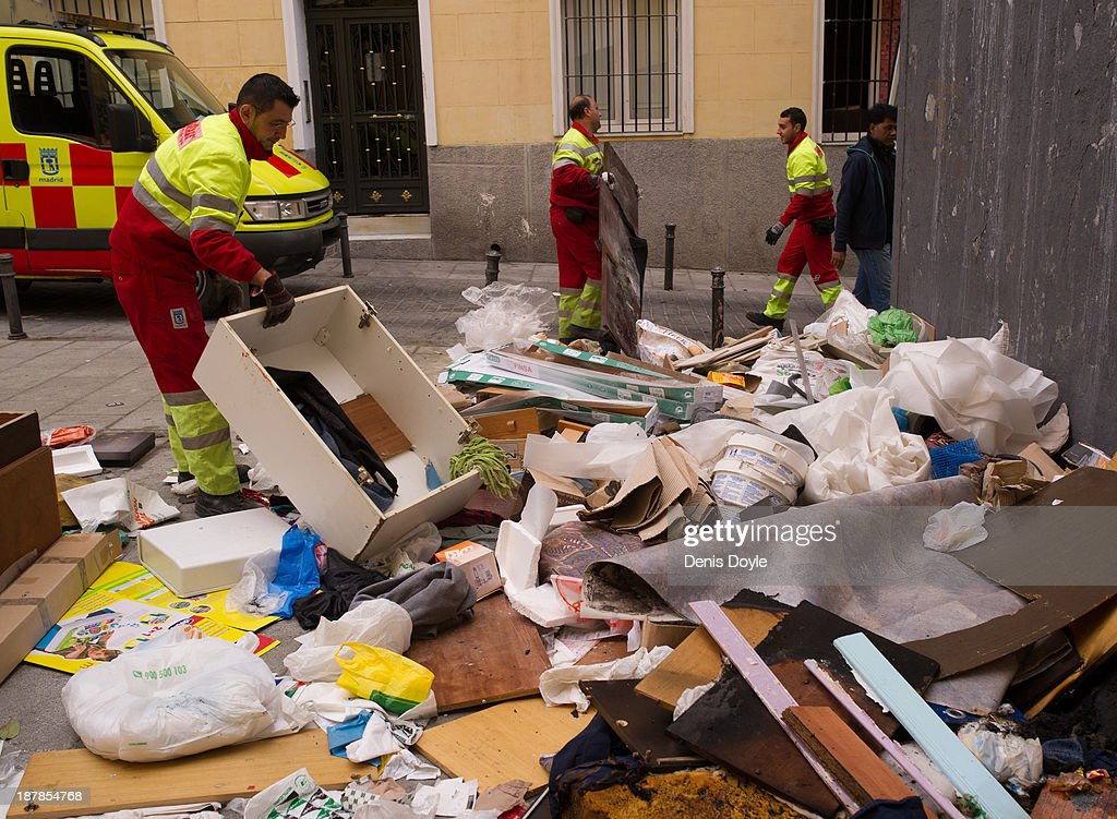 Garbage cleaners provide minimum services collecting rubbish in the Lavapies district of Madrid on November 13, 2013 in Madrid, Spain. Street cleaners, garbage collectors and public park gardeners working for Madrid city council started an indefinite strike 9 days ago after the private contracters plan to axe more than 1,000 jobs and introduce a 40% pay cut for the remaining workers.